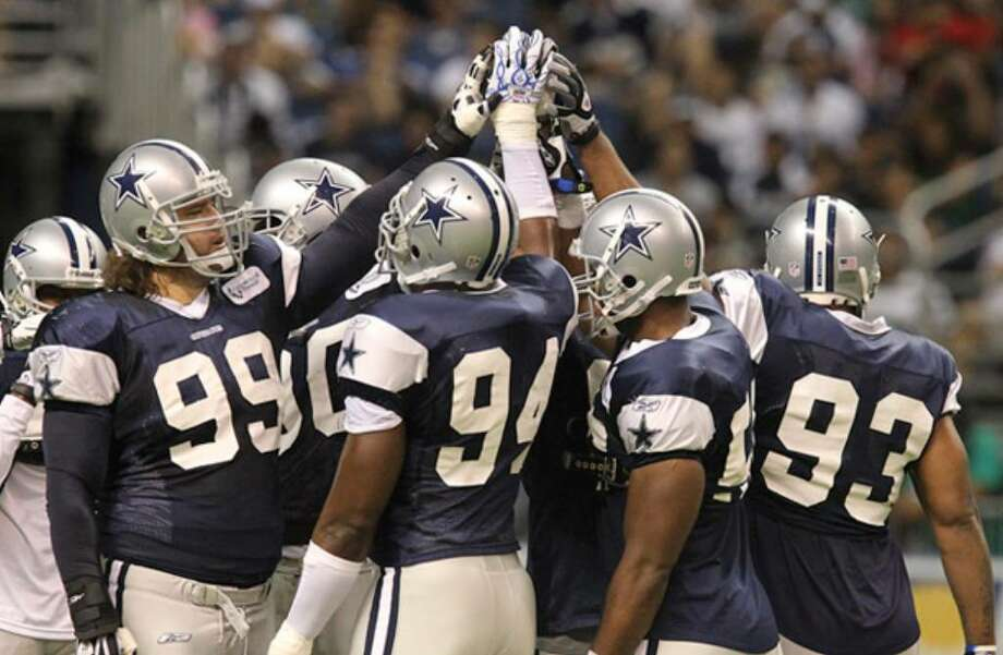 Members of the Cowboys' defense gather before a drill. Dallas returns 10 starters from a unit that allowed just 15.6 points per game last year.