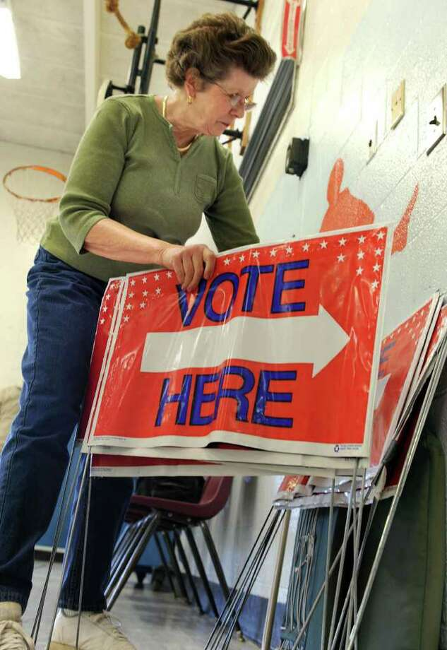 """Sandy Chaleski, an assistant registrar of voters, counts the """"vote here"""" signs that she'll have available for workers to set up Tuesday morning at the Pembroke Elementary School polling place. Photo taken Monday, Nov. 1, 2010. Photo: Carol Kaliff / The News-Times"""