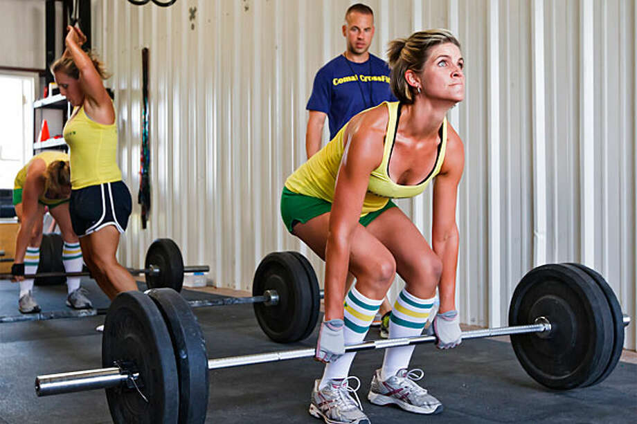 Jennifer Schulz (right) works on a dead lift while Tommy Williams looks on during a workout session at Comal CrossFit. / Prime Time Newspapers 2010
