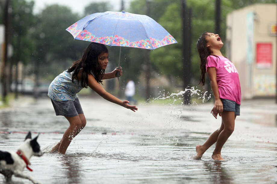 Alexa Beza, 9 (left), splashes her sister, Marissa, 7, from a puddle on Albert Street near Zarzamora as rain bands from Alex passed over the city.