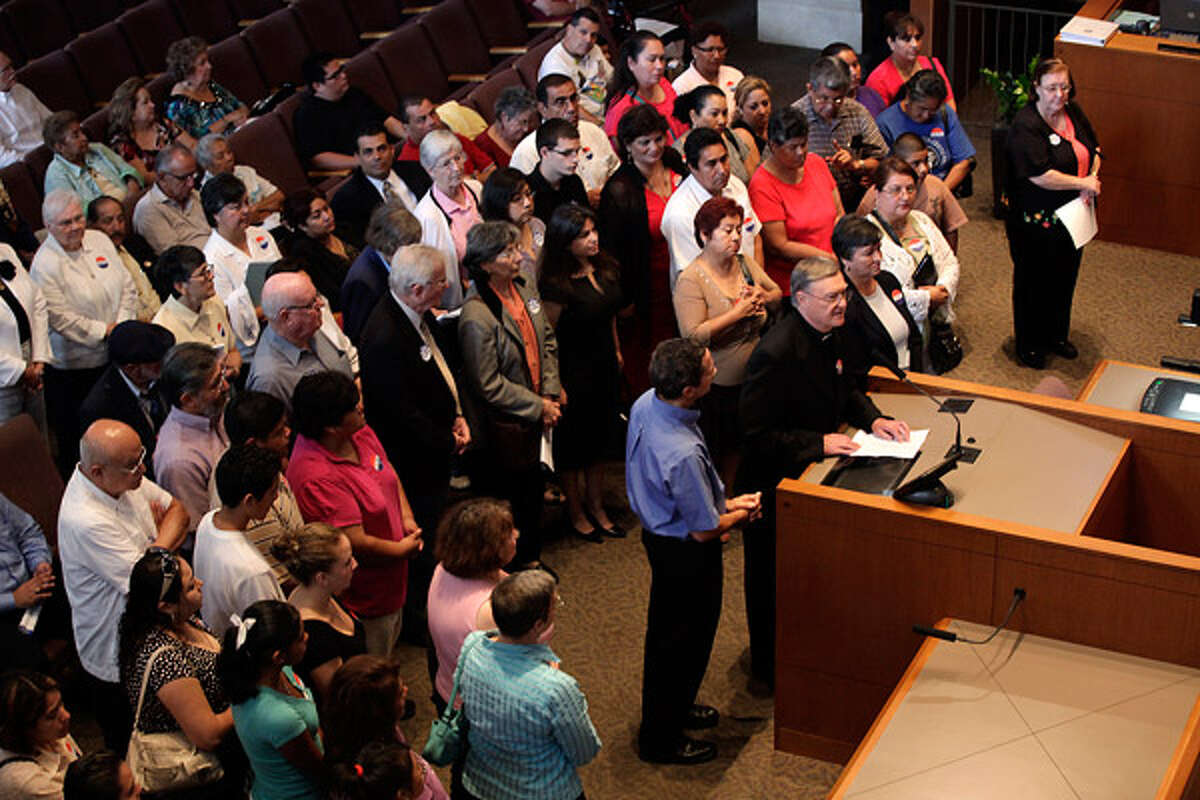 Communities Organized for Public Service members and supporters, led by the Rev. Walter D'heedene (at lectern) and Robert Mueller (standing next to him), address the City Council. The COPS organization favored the resolution, which the council later passed on an 8-3 vote.