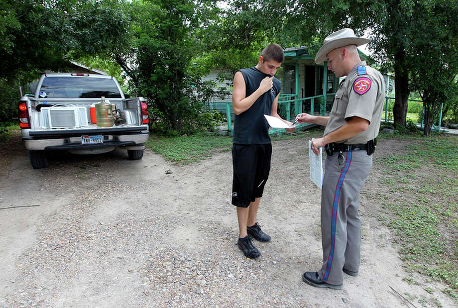 Texas State Trooper Aaron Garza (right) informs Mauro Flores, Jr. about the mandatory evacuation in La Grulla, Texas on Thursday, July 15, 2010. La Grulla was placed under mandatory evacuation as the potential for rising flood waters threatened homes and property along the Rio Grande River. Flores said he and his family were going to take shelter at a family's home located on higher ground. / San Antonio Express-News