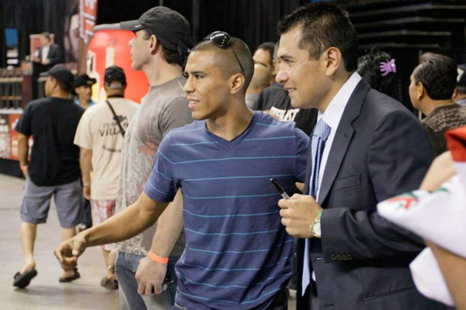 Raul Martinez (left) poses with five-time world champion Marco Antonio Barrera before Wednesday's news conference at the Alamodome.
