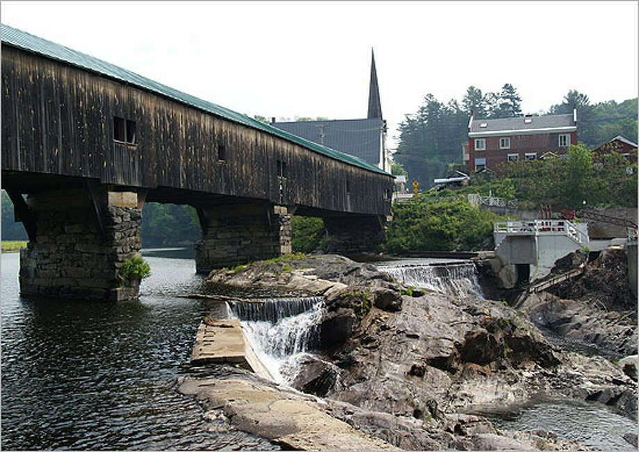 The Ammonoosuc River flows over a dam behind the center of Bath, N.H. The Brick Store (right) is the longest continuously operating general store in the United States. The covered bridge is one of several of the rustic landmarks in the area.