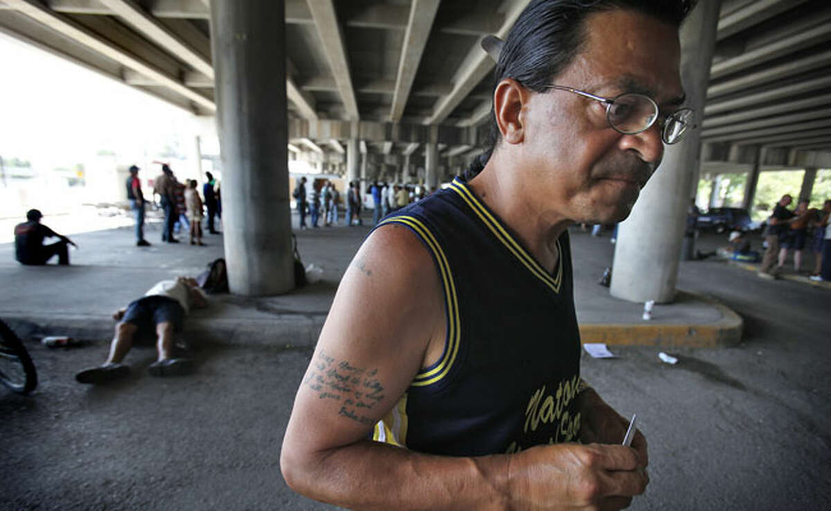 San Cristobal Canales says he stays at the courtyard on and off and needs to go back to the streets for more and better food. Behind him is a line for a meal Sunday under the bridge at Ninth and Alamo streets.