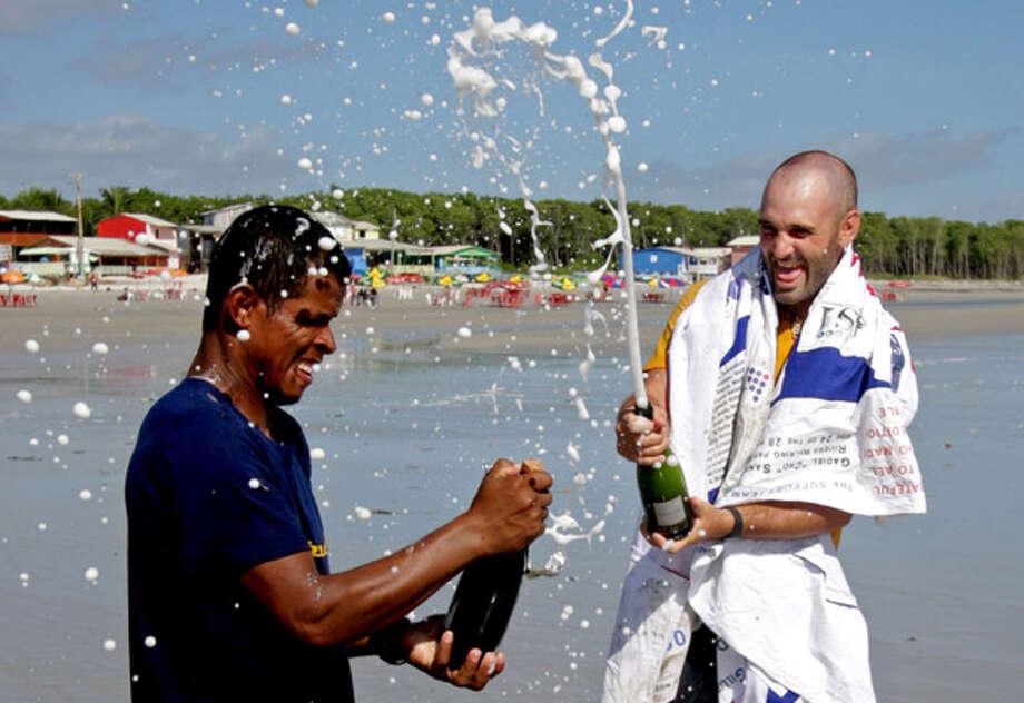"Ed Stafford, of England (right), and Gadiel ""Cho"" Sanchez Rivera, of Peru, celebrate arriving to Crispim beach in Marapanim in Brazil's Para state."
