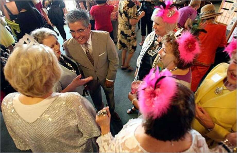 San Antonio Express-News fashion writer Michael Quintanilla chats with the Queens of Fun at the Women's Club on Wednesday.