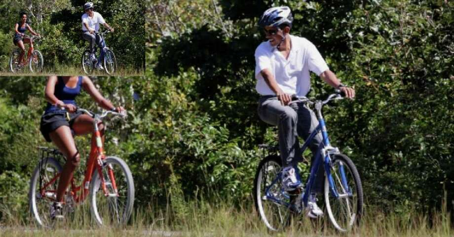 President Barack Obama looks back at daughter Malia as they ride bicycles in Manuel F. Correllus State Forest in West Tisbury, Mass., while the first family vacations on Martha's Vineyard, Aug. 27, 2010.