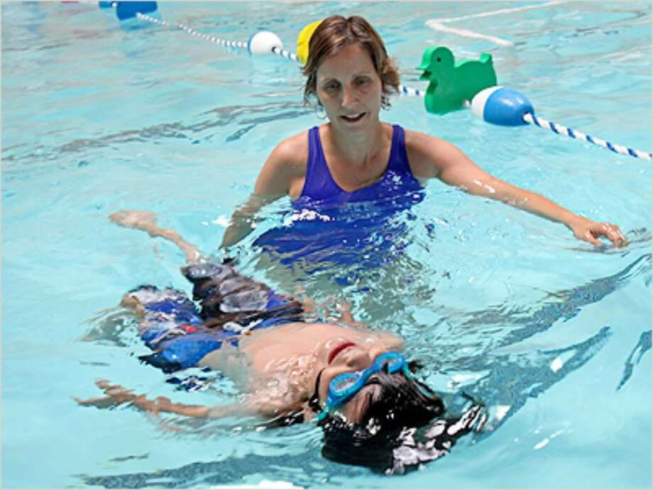 Owner Mary Reilly-Magee watches Diego Camacho swim on his back at Love to Swim and Tumble School in Schertz.