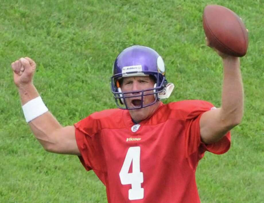 Brett Favre makes a TD signal as he returns to the Vikings' practice field for the first time this year. Favre threw for 4,202 yards last season while setting career bests for fewest interceptions, completion percentage (68.4) and QB rating (107.2).