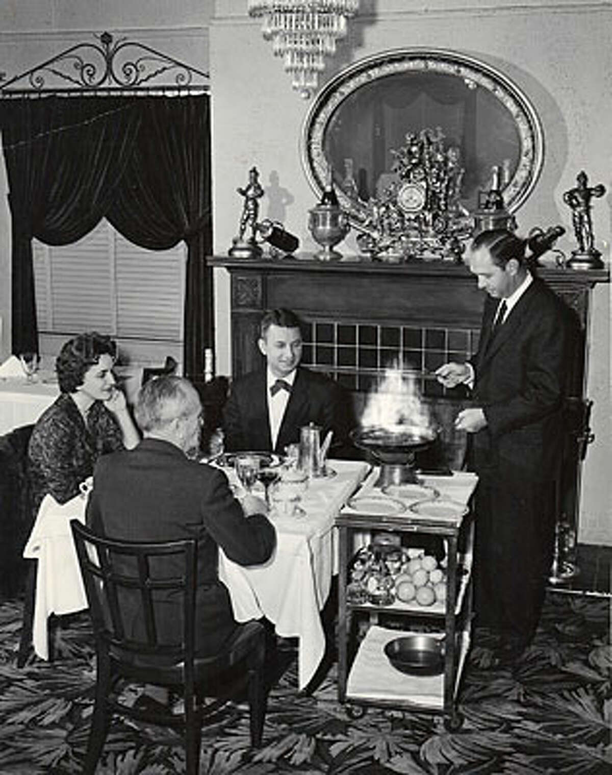 George Dareos (right) flames Crepes Suzette for his brother Pete Dareos, his sister-in-law Irene Dareos and friend Alexandre Jouffray in 1962.