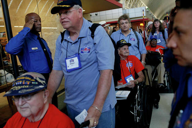 Jeffrey Jung, left, a Navy Veteran, pushes his father, World War II Veteran Lester Jung, as they go through security at the San Antonio International Airport on Friday. Also in line is World War II Veteran William Schroeder, 82, with RN Bryan Watson, and World War II Veteran Calvin Curtis, with Sharon Martin. / SAN ANTONIO EXPRESS-NEWS