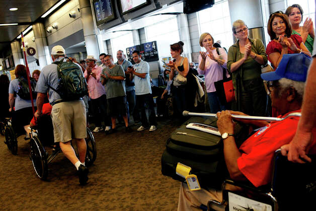 Travelers waiting for their flights clap and cheer for World War II Veterans including Calvin Curtis, 85, right, as they arrive at their gate. / SAN ANTONIO EXPRESS-NEWS