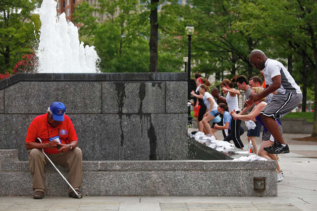 World War II veteran, Calvin Curtis, 85, who served with the Marines, rests while the Navy Memorial is used as a workout station on Saturday. / SAN ANTONIO EXPRESS-NEWS
