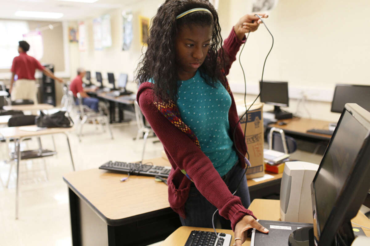 Jaleisha Smith, who will be a junior at Judson High next year, helps prepare computers at Wagner High School for next year as a Judson ISD summer intern.