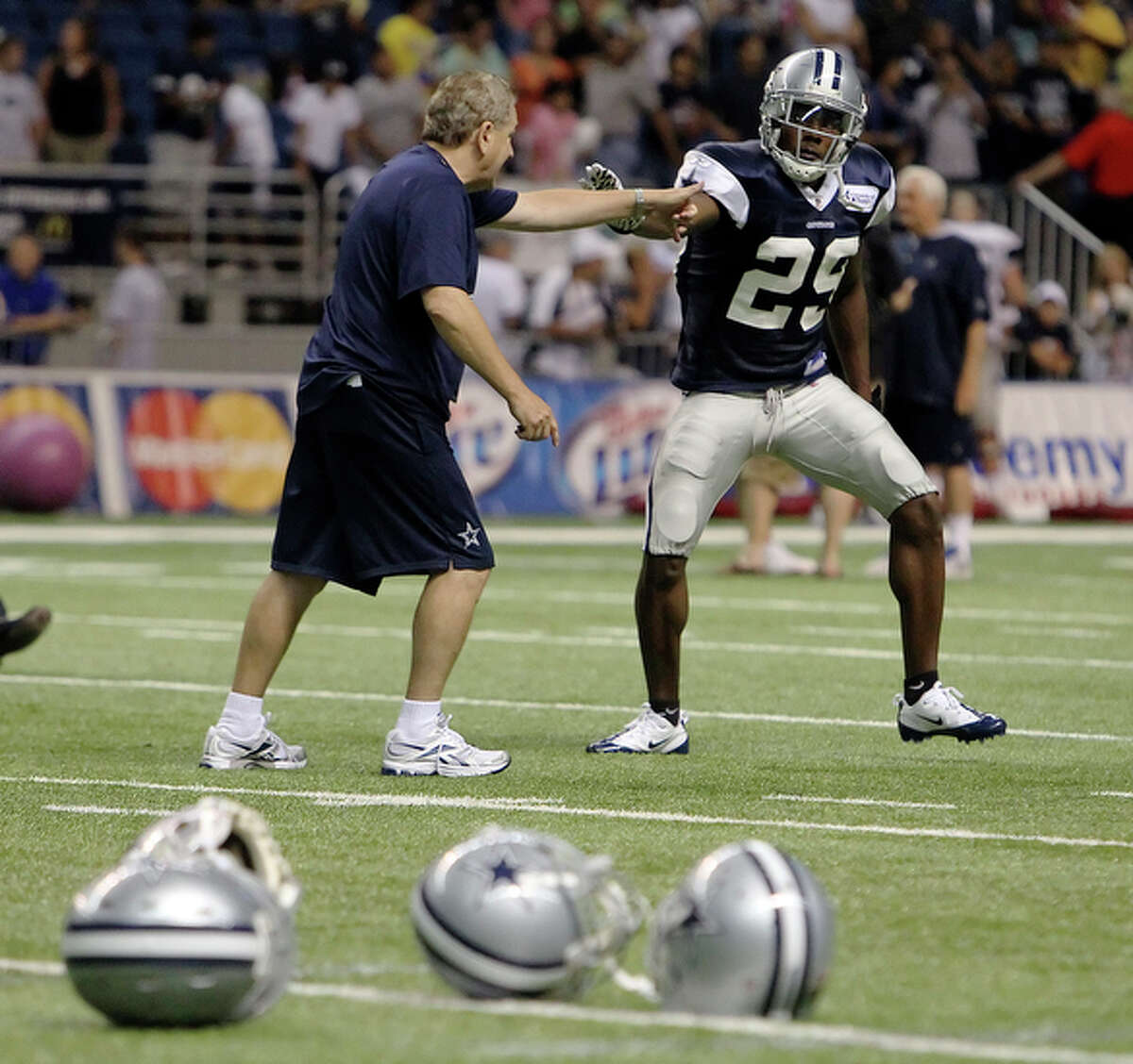 UTSA's Teddy Williams (29) gets an after-practice tutoring session with secondary coach Dave Campo at the Dallas Cowboys training camp at the Alamodome Thursday