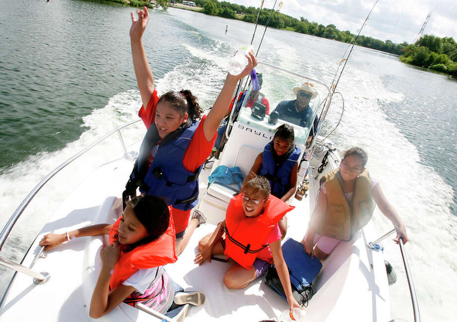 Catalina De La Cruz, 9, left front, Harley Pesina, 10, left center, Gabriela Nino, 9, center, Deonna Penn, 10, right back, and Serena Pruitt, 10, take in the boat ride out from shore during the Flotilla Boating and Fishing Club Kids Fishing Tournament at Calaveras Lake for the San Antonio Boys and Girls Club on Wednesday, July 21, 2010.