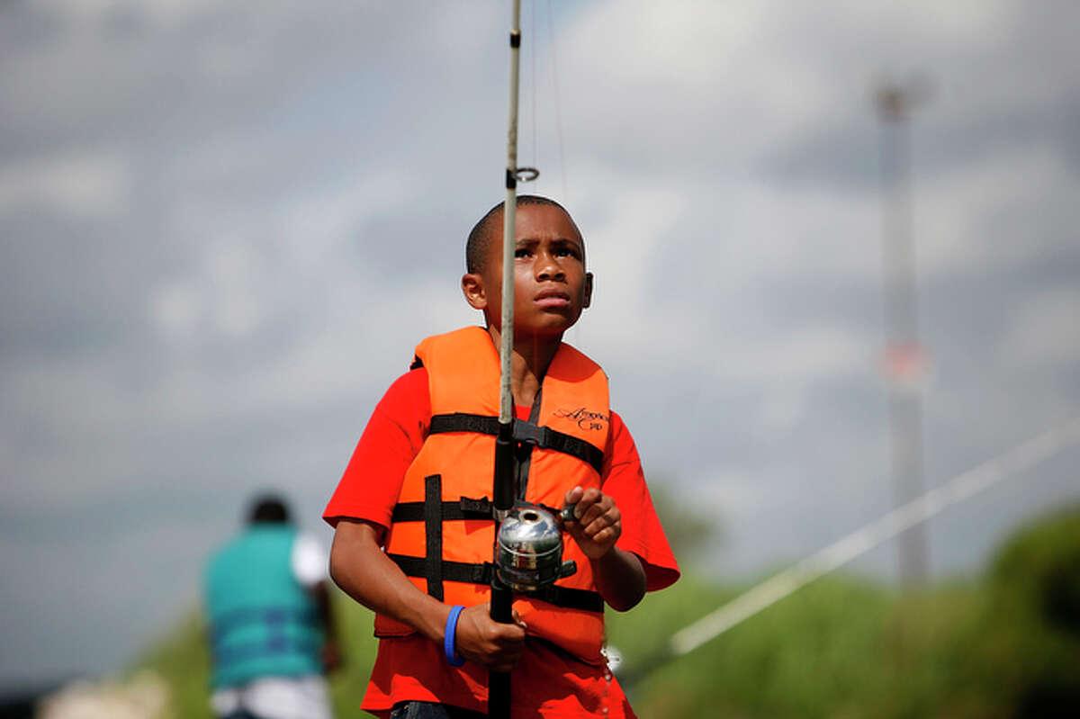 T. J. Polk, 9, checks his fishing rod before casting it.