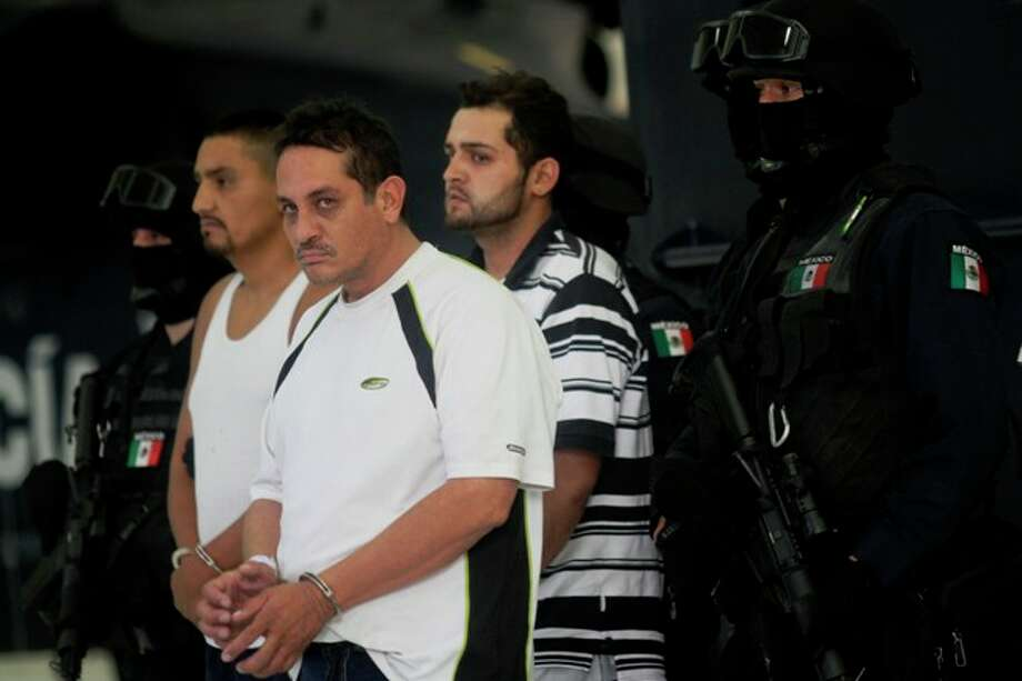 """Jesus Ernesto Chavez, known as """"El Camello"""" (second from left) stands as he is guarded by federal police during a presentation to the press, in Mexico City, Friday, July 2, 2010. According to the federal police Chavez ordered the March 13 attack that killed a U.S. consulate employee and her husband as they drove in the violent border city. The other two detained men are unidentified."""