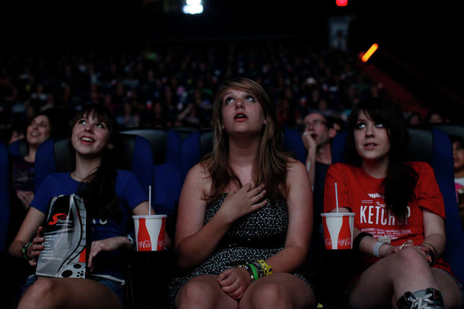 Erin Biediger, 14, from left, Julienne Bajusz, 13, and Taylor Dean, 13, sing during the Grease Sing-A-Long at the Santikos Palladium IMAX at The Rim in San Antonio on Thursday, July 15, 2010. / SAN ANTONIO EXPRESS-NEWS