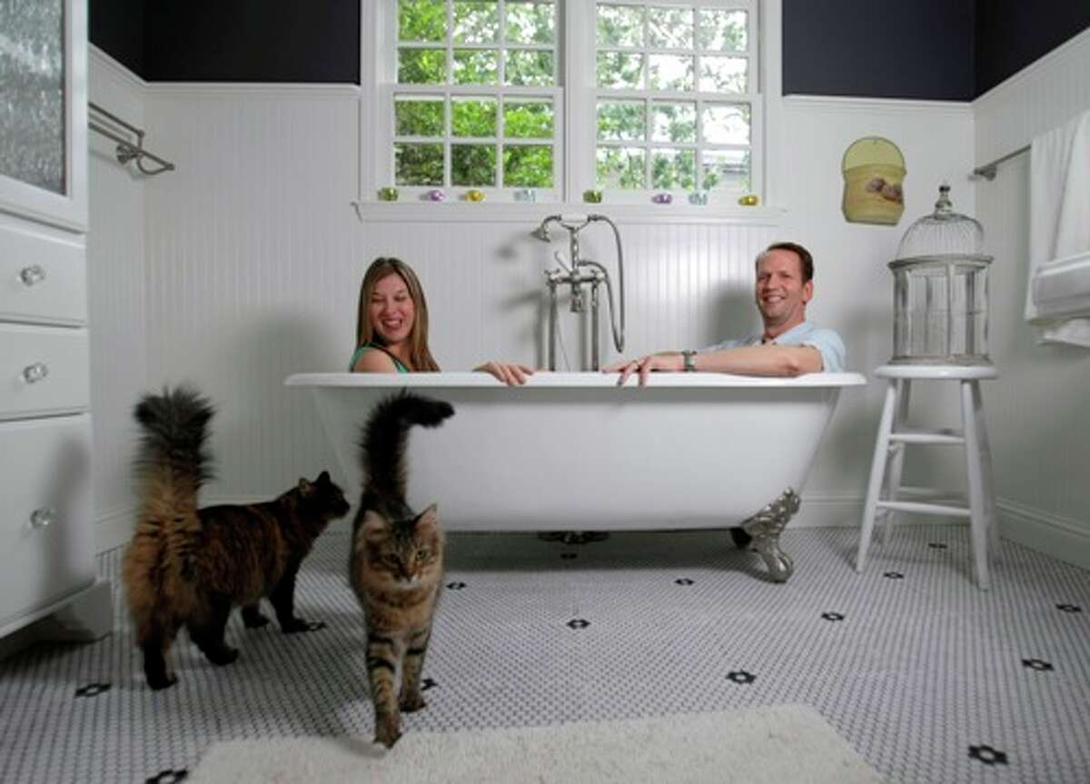 Cats Ron and Nancy walk by Dwayne and Sarah Van Wieren as the two sit in a claw-foot tub in their new home, which they qualified for with 100 percent financing and no money down.