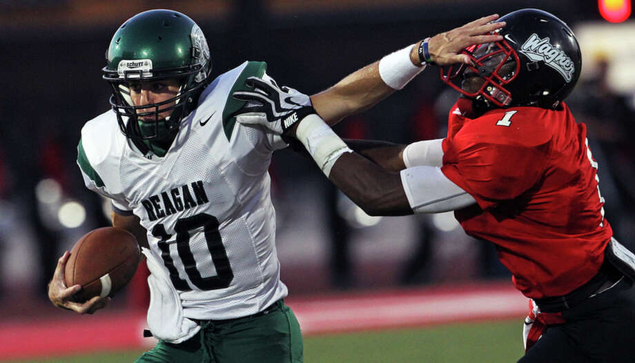 Reagan quarterback Trevor Knight stiff arms Naeem Martin around right end. / © 2010 San Antonio Express-News