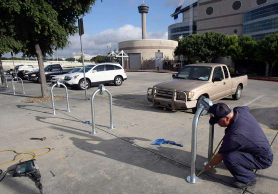Charles Finch of Horizon Custom Products takes measurements while installing bike racks near the Alamodome.