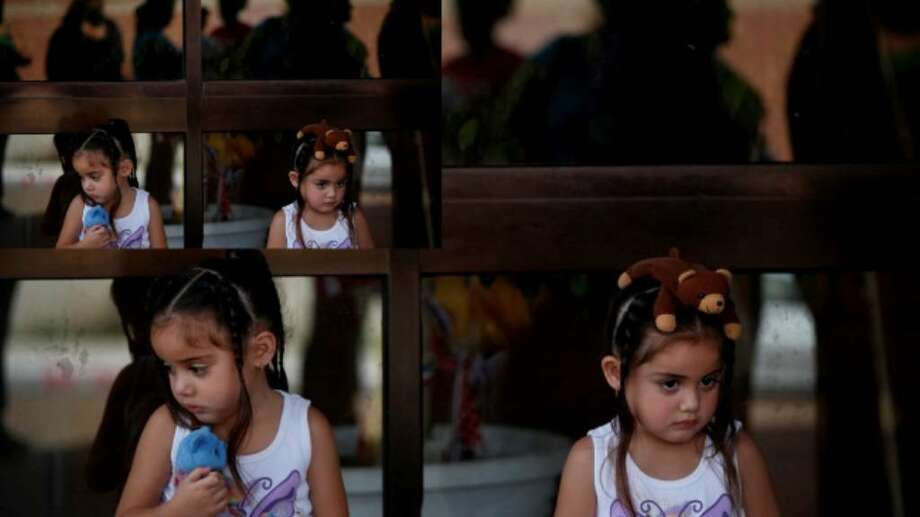 Three-year-old twins Alyssa (left) and Alyza Garcia wait to visit their father at the Bexar County Jail on Saturday.