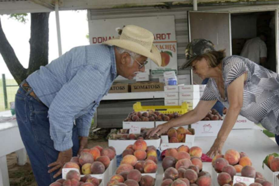 Roman and Lupe Castro, from Big Spring look over the peaches available at the Donald Eckhardt Orchard stand on Highway 87 just west of Fredericksburg, Thursday.
