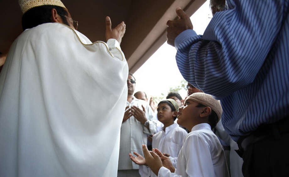 Led by Imam Ameen Aziz (left), men and boys pray during the opening of the new Al-Madinah Mosque, the centerpiece of the Muslim Children Education and Civic Center on the Northwest Side, on Aug. 13.