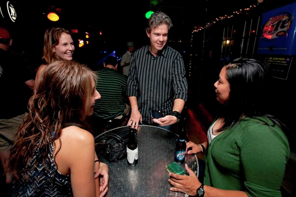 Bret McGowen (center) and Amy Collins (left, rear) try to get patrons of Rebar to take on a task that the app BarCards has suggested on their I Phone.