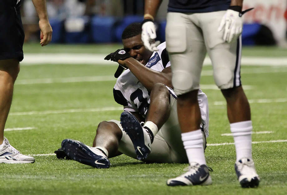 Receiver Dez Bryant grimaces after suffering a high-ankle sprain during practice at the Dallas Cowboys training camp at the Alamodome on Friday, July 30, 2010. Bryant is believed to be out four to six weeks recuperating from the injury. / San Antonio Express-News