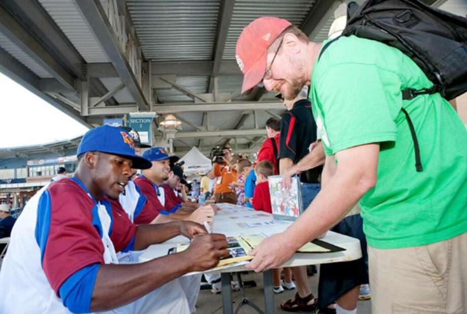 Midland RockHounds outfielder Archie Gilbert autographs a baseball card for Jeff Beg at the Texas League All-Star Game.