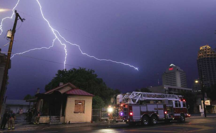 Lightning strikes over a home that was believed to have been struck by lightning according to firefighters from Station No. 3 on the scene at Camaron and Travis near downtown. The home was vacant and listed for sale.