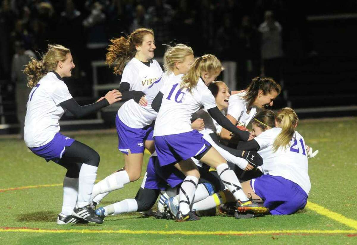 The Westhill team piles onto goalie Jennifer Osher after winning as Westhill and Darien face off in the FCIAC girls soccer semifinals at Wilton High School in Wilton, Conn., Monday, November 1, 2010. Westhill won in a shootout.
