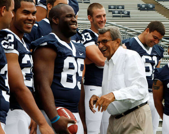 Penn State coach Joe Paterno laughs with some of his players, including (from left) Evan Royster, Ollie Ogbu, Brett Brackett and Stefen Wisniewski. Paterno has 394 wins entering the 2010 season.