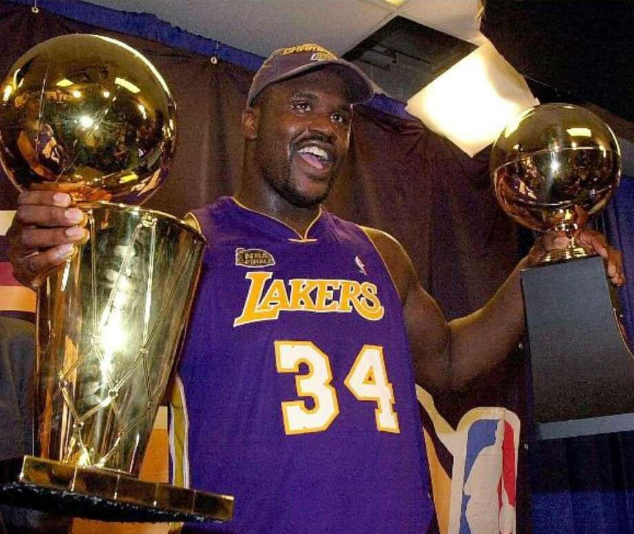 Shaquille O'Neal holds the Finals MVP trophy (right) and Larry O'Briean Championship trophy after the Los Angeles Lakers beat the Philadelphia 76ers to win the NBA title in 2001 — one of his three rings with L.A.