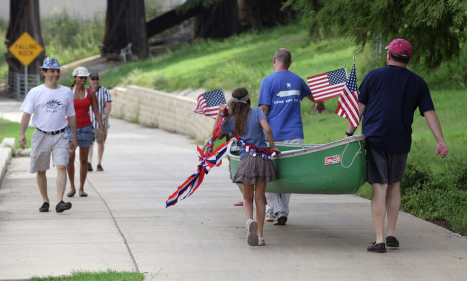 Boaters take their canoe down to the San Antonio River for the annual July 4th King William Yatch Club paddling of the Eagle Land section of the San Antonio River, July 4, 2010. / SAN ANTONIO EXPRESS-NEWS