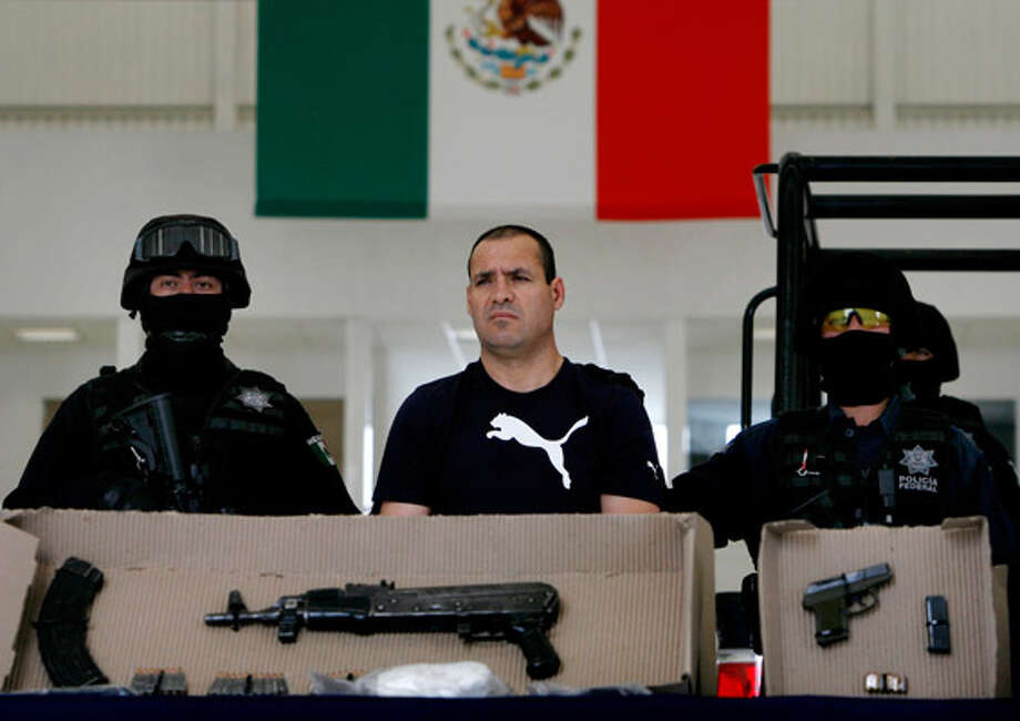 Police show Luis Vazquez Barragan and weapons they say they seized from him to the press in Mexico City after his arrest. They say he's a top member of La Linea gang, the enforcement arm of the Ju?rez cartel. La Linea is blamed in a recent car bombing that killed three people in Ju?rez this month.