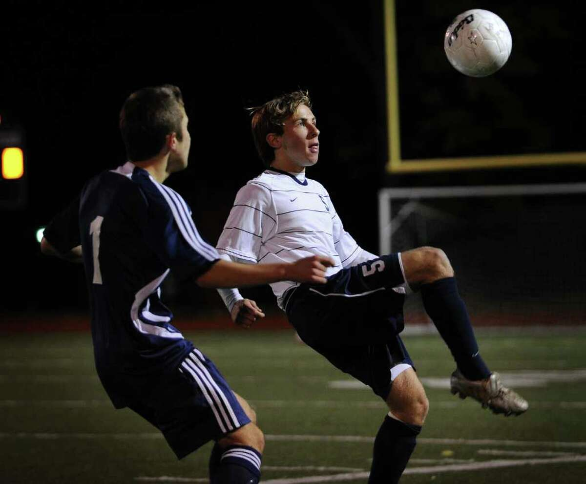 Staples' Jake Malowitz plays the ball in front of Wilton's Robert Aravena during the FCIAC boys soccer semifinals at Fairfield Ludlowe High School on Monday, November 1, 2010.