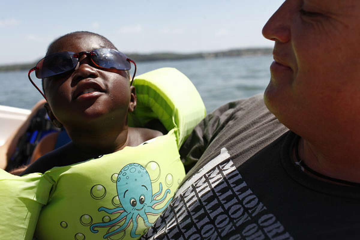 Kiefer Patterson, 2, with his adoptive father, Matt Patterson, on a boat during a gathering of Haitian children now living in the San Antonio area at the home of John Leininger on Lake LBJ in Marble Falls.