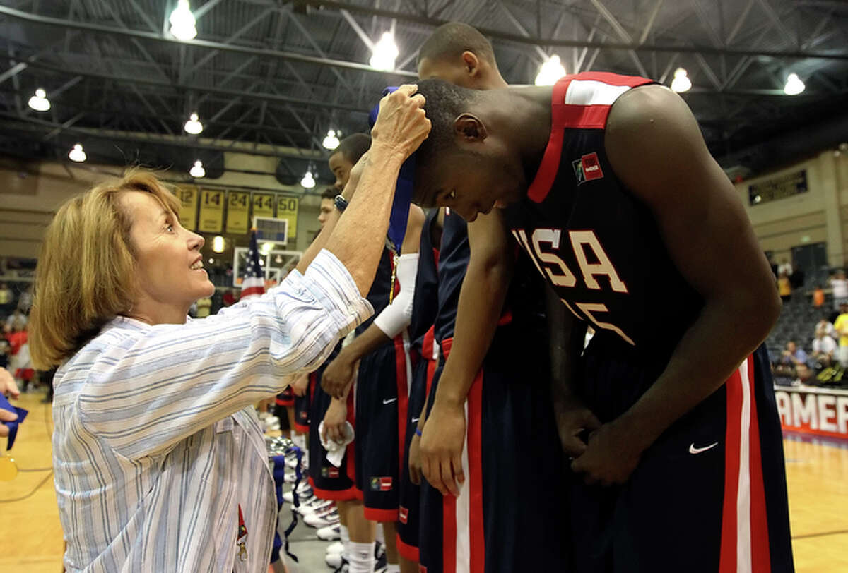 San Antonio Sports Foundation Executive Director Susan Blackwood (left) places a gold medal on Team USA's Pat Young (15) after the USA team defeated Brazil in the final game.