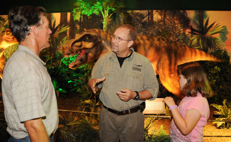 George Blasing, also known as Dinosaur George, helps visitors -- such as Mark Veltman and daughter, Katherine, 9, of Corpus Christi -- to better understand the popular exhibit.