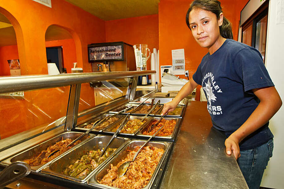 Juany Rodriguez makes sure trays of taco fillings are full and fresh at Comal County Tacos.