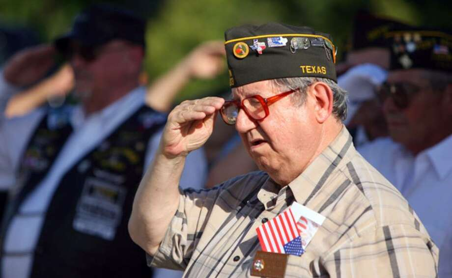 Leonard Childs, a member of VFW Post 9603, salutes as a flag is retired during the ceremony at VFW Post 837.