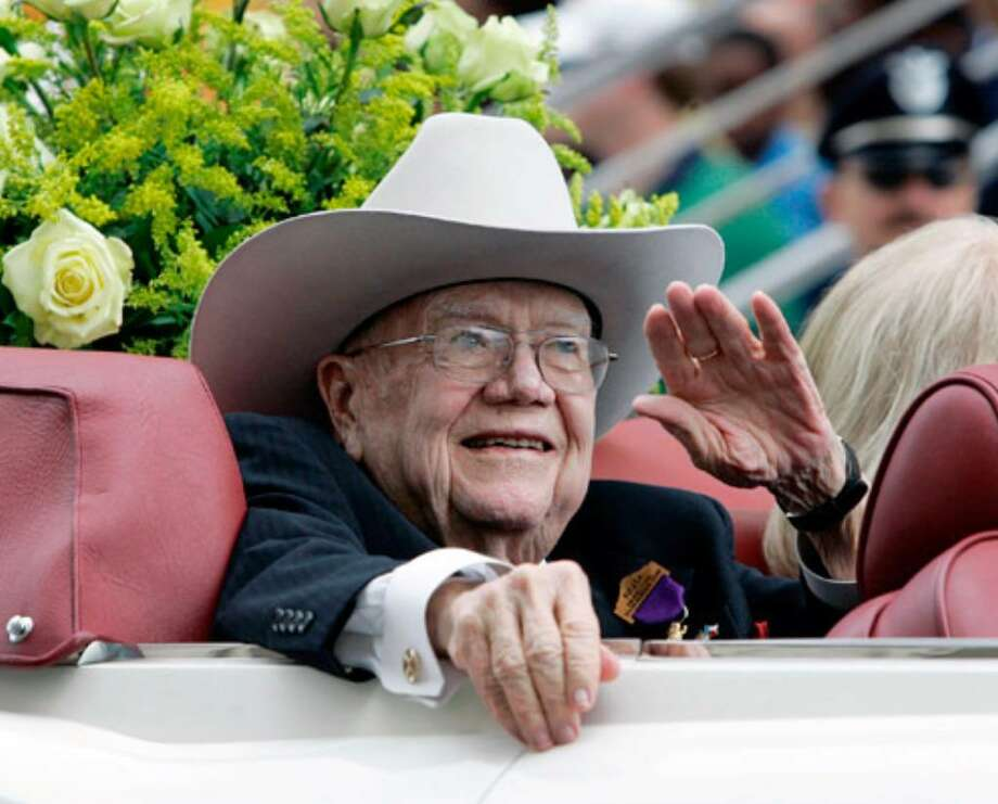 Former Gov. Dolph Briscoe waves from his vehicle as honorary grand marshal of the 2008 Battle of Flowers Parade. Briscoe graduated from the University of Texas at Austin in 1942 and served in the China-Burma-India theater during World War II.