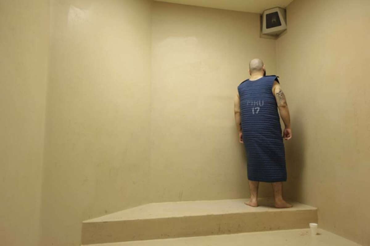 A Bexar County Jail prisoner stares at a corner while wearing a safety smock, which is used to keep mentally inmates from hurting themselves. He's in the lockup's Mental Health Unit, an austere, 18-cell wing where a psychiatrist visits once a day.