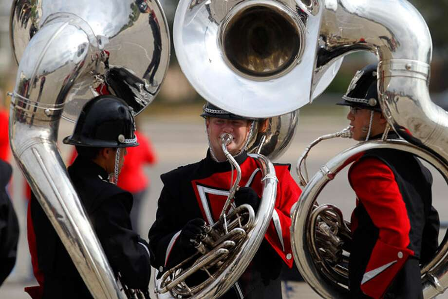 Cullen Burkett, 15, practices the tuba with fellow members of the Argyle High School Marching Band in the Alamodome parking lot.
