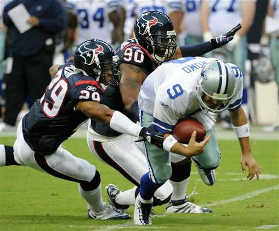 The Texans' Glover Quin (29) and Mario Williams reach in to sack  Cowboys quarterback Tony Romo (8) during the first quarter of an NFL preseason football game Saturday.