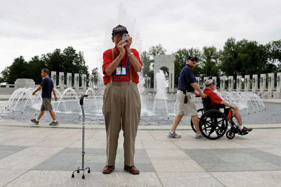 John Buchanan, 89, who served in the Navy during World War II, photographs the World War II Memorial as Jeffrey Jung, also a Navy veteran, pushes his father, Lester Jung, 87, a B-17 pilot during the war.